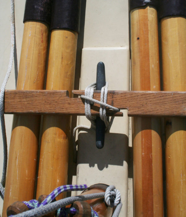 The crosspiece holding the oars has two jam-cleat-like notches for quick locking of the lashing to the cleat below.