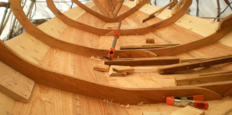 The garboards are built up of three planks joined with flush dory bevels and rivets. The seams between them are visible here with one running out at the transom and the other at the garboard's upper edge. To the far left is one of the butt blocks on the broad strake.