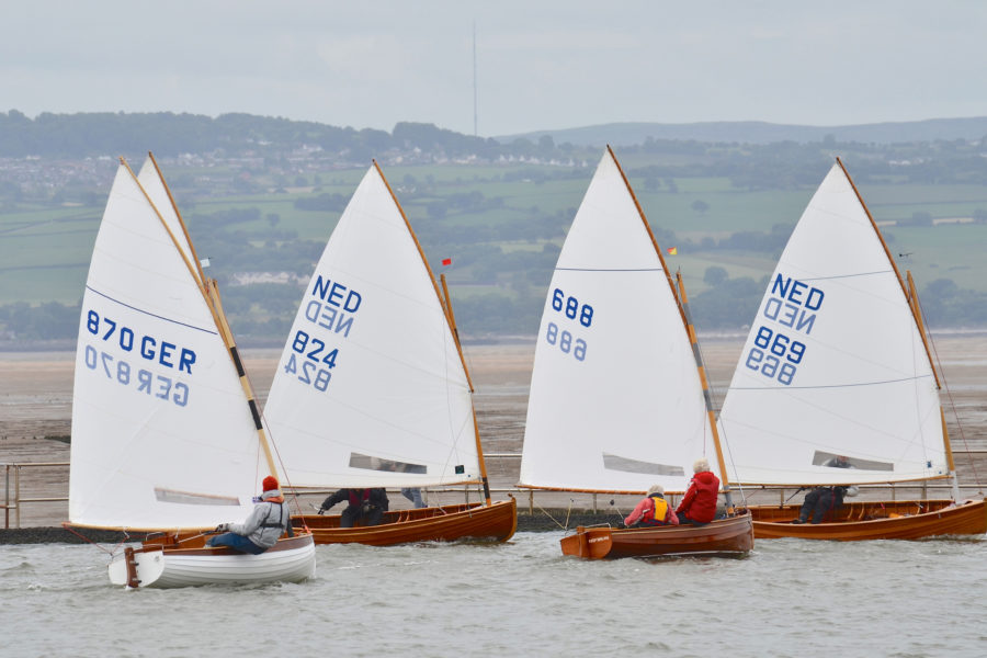 Five dinghies come about in the 100th anniversary race at West Kirby. The woman skippering the Dutch entry #688 is 81 year old Tonnie Surendonk.
