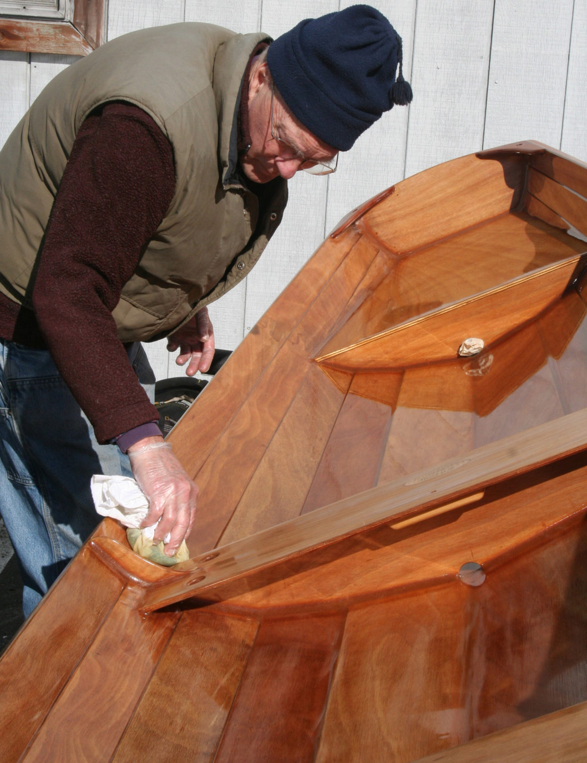 "The varnish is wiped on in ""panels."" Here Don is applying varnish to the planks bordered by the thwart frame and the transom and stern seat compartment."