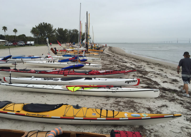Over 100 kayaks, canoes, and sailboats lined up on the beach for the 2015 Everglades Challenge. The Sunshine Skyway Bridge in the distance spans the entrance to Tampa Bay.