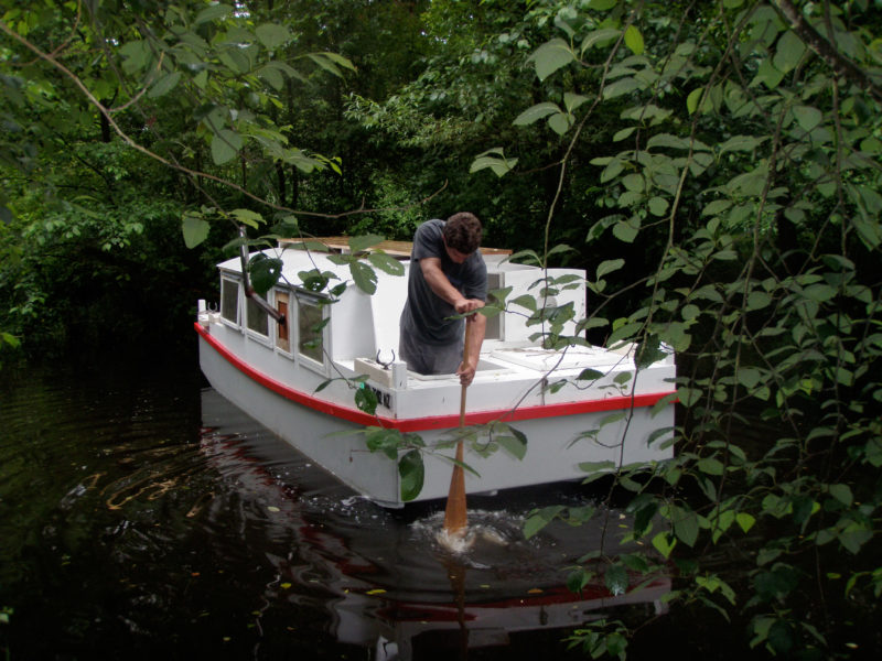 The Escargot is not a petite boat but its shallow draft gets it into some small waterways. Standing in a forward hatch, Nate explores a backwater frequented by beavers but not by boats.