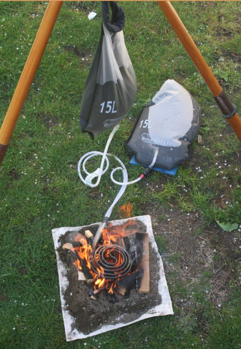 The supply bag needs to be elevated about 3' to provide the coil and thermostat with an adequate flow of water. Here it is suspended from a tripod of oars.