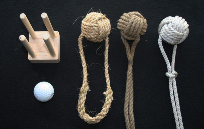 "While a monkey's fist can be tied by starting the wraps around your fingers, a simple jig makes the process faster and easier to master, especially with soft line like the braided nylon. The jig here is for a golf-ball core and ¼"" line. The 7/16"" dowels—just large enough to provide clearance for the third set of wraps—are set outside of the perimeter of a 1 7/8"" circle for a loose fit around the 1.68"" ball. The finished monkey's fists are, from left to right: sisal, finished with a spliced loop; poly, with the tail whipped to the heaving line; and braided nylon. Only the poly monkey's fist floats."