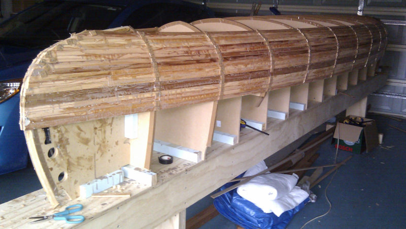 The bead-and-cove cedar strips kept the seams tight around the turn of the bilge.