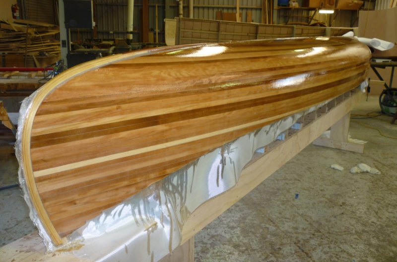 After Andy applied fiberglass and epoxy to the hull, the canoe sat idle until he brought in friends to help with the finishing touches.