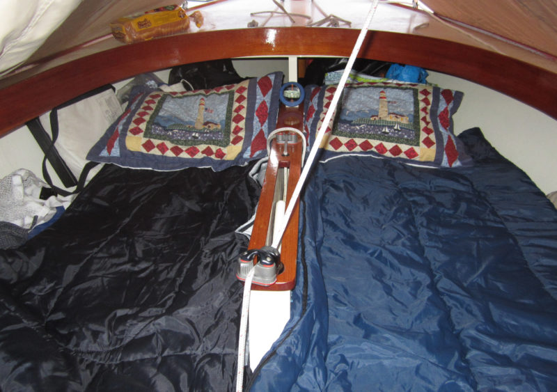 The Marsh Cat's broad beam makes the cockpit sole wide enough to sleep two flanking the centerboard trunk. A boom tent provides cover.