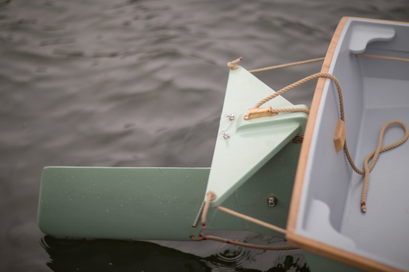 The rudder is controlled by lines threaded through the transom and frames, allowing the boat to be steered from any position in the boat.