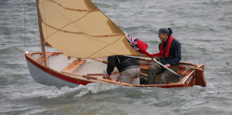 While the builder mans the helm and the sheet, the crew keeps his weight aft and is ready to respond to gusts.