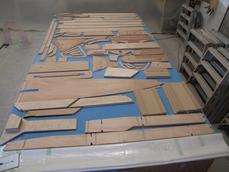 The kits include all of the precision cut okoume plywood parts for the boat, including foil-shaped rudder and daggerboard blades, and for the strongback, including the legs to bring it up to a convenient working height.