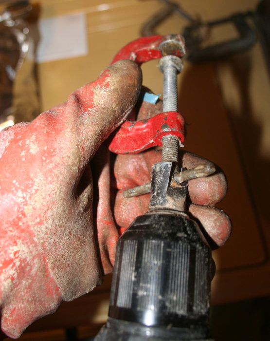 A cheap plug cutter and a cordless drill make it easy to spin the screw quickly to strip the epoxy from the threads.