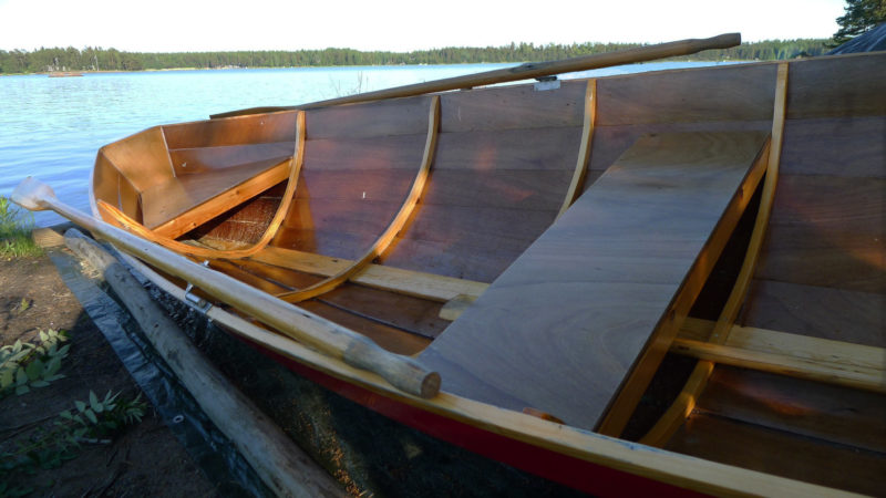 Traditional Finnish rowing boats had closely spaced steam-bent frames. The Saajuu's glued-plywood lapstrake construction allows the use of widely spaced laminated frames. The folding tholes set the oars on the gunwales when not in use.