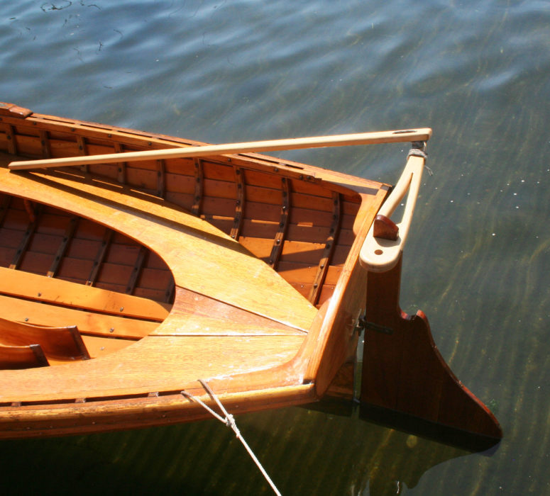 A straight transverse tiller long enough to extend past the transom opens up the tern sheets for a passenger. The hole in the tiller on the port side of the rudder head is for a flagstaff.