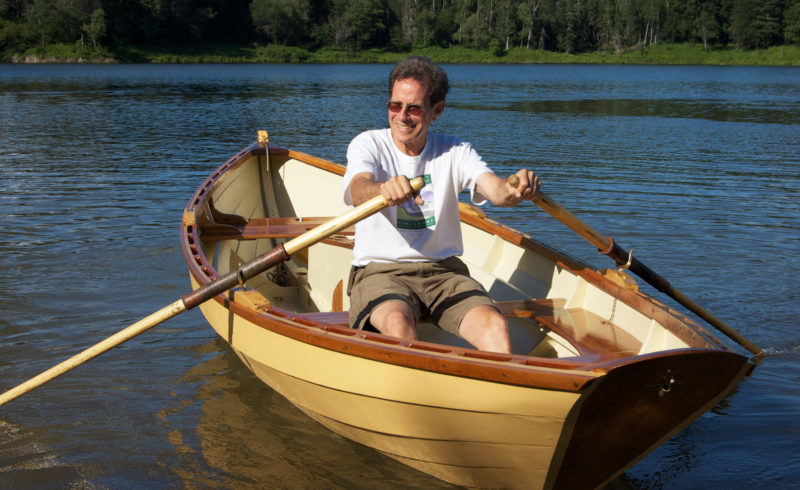 """On launch day, I was a happy builder aboard Nona Belle. The oars are solid (not laminated) white ash (Fraxinus americana), and fashioned from two rough-cut, full 2"""" x 8' planks. I sewed the leathers and buttons together with sail twine—no brass tacks used—to avoid putting holes in the wood."""