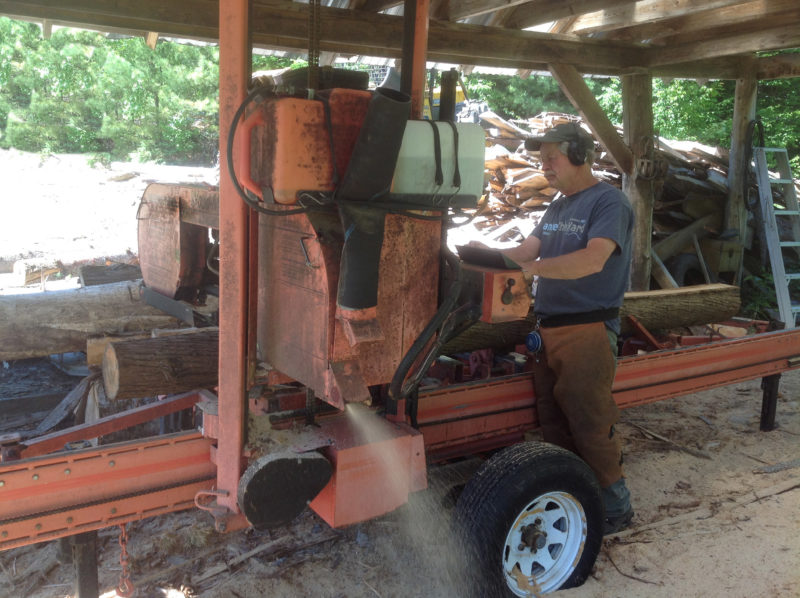 """Bill Manning operates his Wood Mizer portable sawmill, milling out planks of white cedar. The rough planks are milled at 5/4"""", to be planed later to final strake thickness of 9/16""""."""