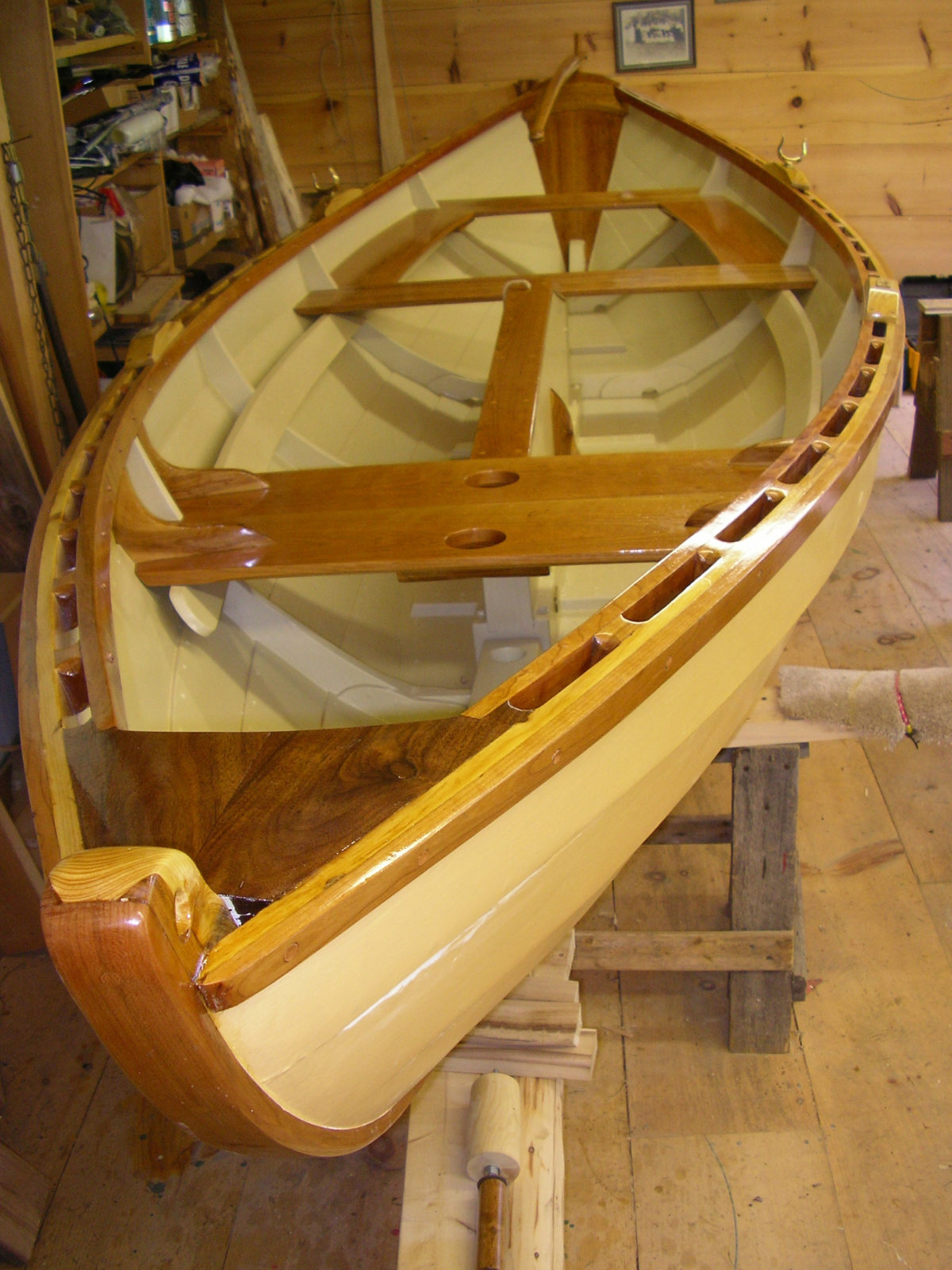 Ready for the water. Gleaming under the varnish is cherry (false stem, thwarts, gunwales), black walnut (Juglans nigra) (breasthook), black locust (Robinia pseudoacacia) (oarlock pads), and apple (knees). Note the two holes at the mast-partners – the mast can be shifted fore or aft depending on the boat load.