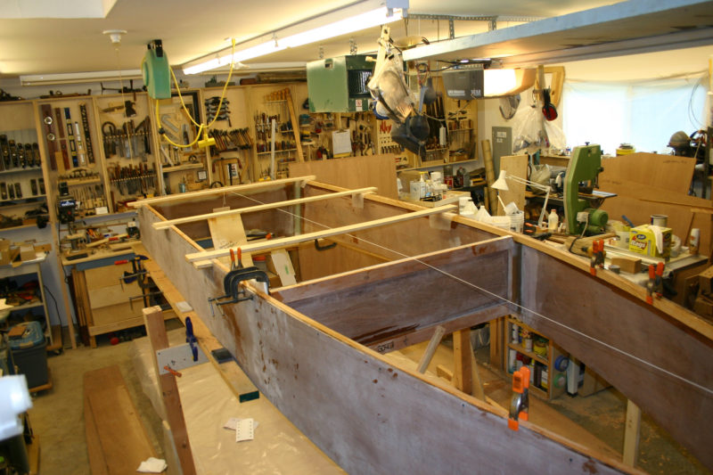 The sides, sprung to the transom, bulkhead, and stem, and constrained by a pair of temporary spreaders, determine the shape of the bottom.