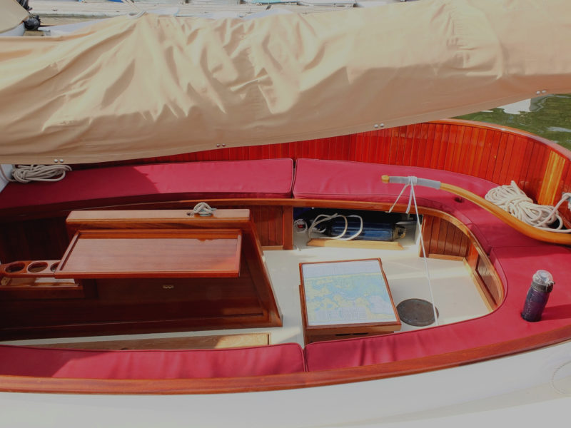 The spacious cockpit provides a table alongside the centerboard, a chart table topping the housing for the electric motor, and drink holders sewn into the cushions.