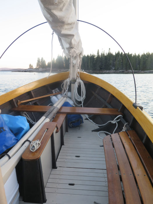 Floorboards provide a reasonably good sleeping surface, but a purpose-made boat bunk is more comfortable. Here, the mainsail is rolled around its yard and slung between the main and mizzen masts. With thole pins removed, a tent pole set in the vacant holes arches from one side to the other to provide a generous interior space. The tent cover is omitted here for clarity.