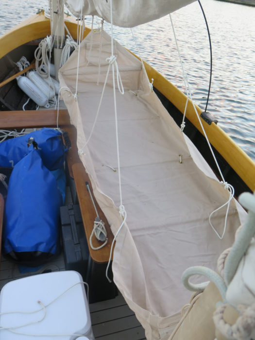 Lines pass over the main yard and are made off to keep the sides and ends vertical. Note the short lines passed through grommets inside the bunk—they tie the slats to the oars.