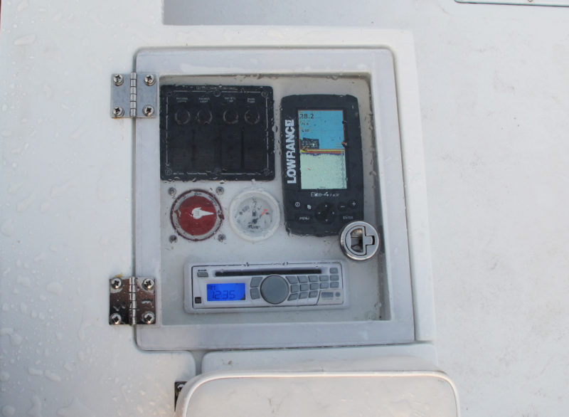 The instrument panel includes switches for lights and bilge and bait-well pumps, flush-mount GPS/fishfinder, CD player with AM/FM radio, master electrical switch, and fuel gauge.