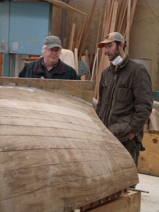 Pete Leenhouts, then the school's director, and author Ben Kahn contemplate widening gaps in the planking seams and the looming deadline for the completing the boats.
