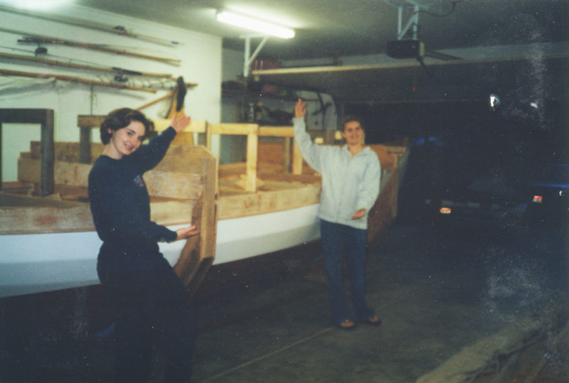 """Daughters Erin and Sara, looking for work as game-show hostesses, show the recently righted hull. Planking is 3/8"""" Douglas fir marine plywood sheathed in fiberglass and epoxy."""