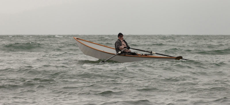 Author Dale McKinnon, in her sliding-seat equipped light dory, makes her way into a headwind and waves,