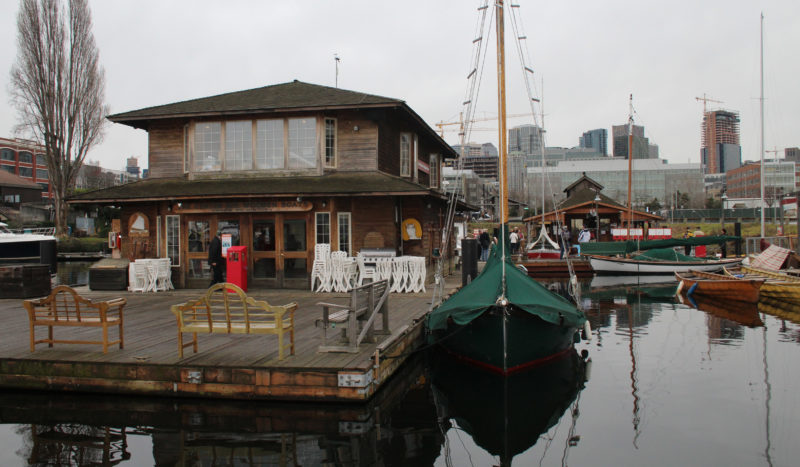 The center's main building is anchored on Lake Union surrounded by a fleet of wooden boats. The site for the new education center is marked by a green fence in the background on to the right of the boatshop.