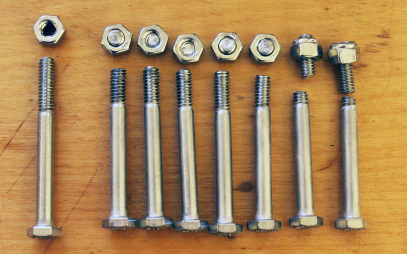 Eight stainless-steel 1/4 x 20 bolts, seven nuts seized up by galling