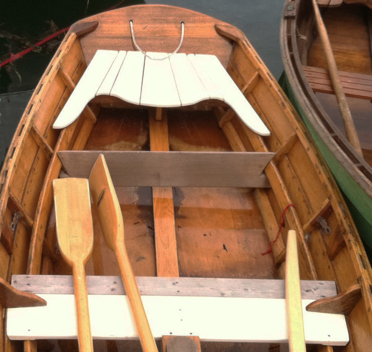 This flat-bottomed skiff has a footboard fit around the risers and resting against a frame.