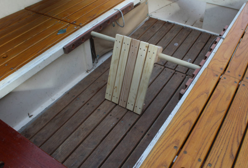 The side benches in this plywood boat have parallel sides so the supports for the stretcher can be long and serve two closely-spaced rowing stations. The holes in the port-side support are notched for removing the dowel.