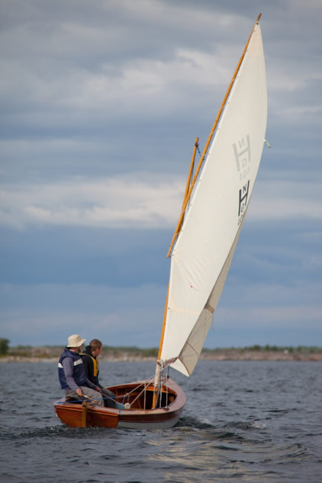 Our Coquina, AANAR, has the Herreshoff-designed hull, but has been rigged with single lugsail. Without the mizzen in the way, we could use a tiller rather than rope steering system Herreshoff used. The Coquina is lively and fast, small enough to be sailed alone also. For the first two years we used her mainly for daysailing and taking part in RAID Finland, but then took up camp-cruising.