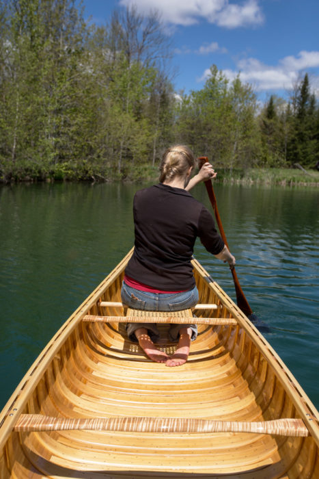 """Elisa Schine worked as an instructor at a wilderness canoe camp before landing at Northwoods Canoe Company. She recently took her boyfriend on his first canoe trip and chose to borrow one of Rollin's Atkinson Travelers instead of using the round-bottomed Prospector she owns because of the Travelers' stability and ease of handling: """"I didn't want to tip him into the river the first time he got into a canoe."""""""