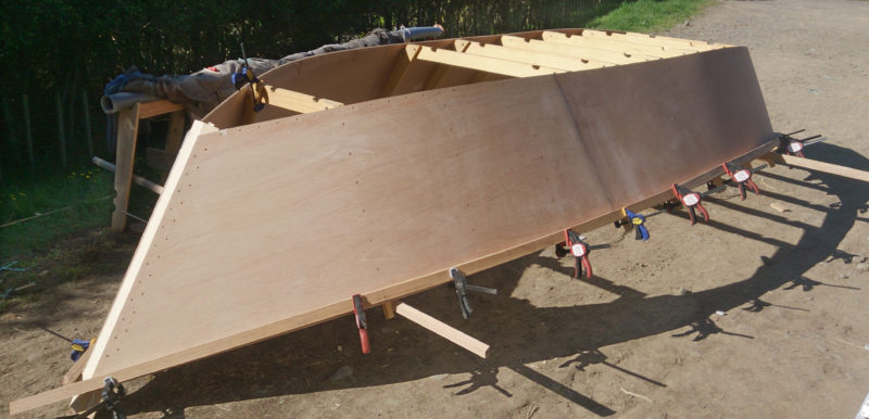 On a sunny New Zealand morning outside the sheep shed we assembled the first free-form hull. We immediately began using the hull as a form on which to steam-bend the chines and gunwales.