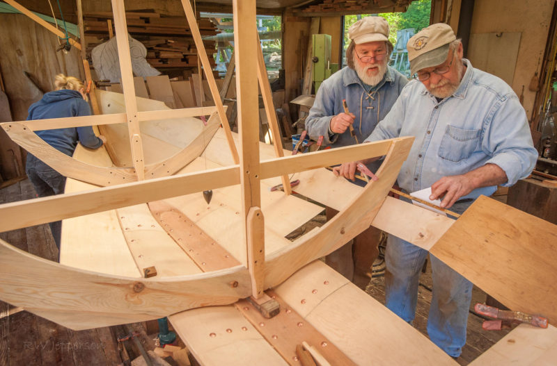 With Jay looking over his shoulder, Vern Lauridsen prepares a pattern for the third strake's forward plank sections.
