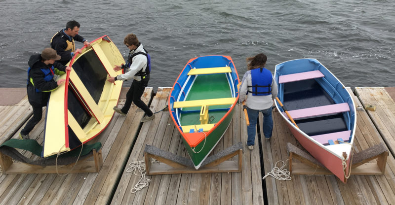 Richard and two students roll MISSY D alongside ANDREA McCOY. The pink and blue boat at the right is GLOBAL EXPLORER, a Bevin's skiff built previously by students of New Bedford's Global Learning Charter Public School.