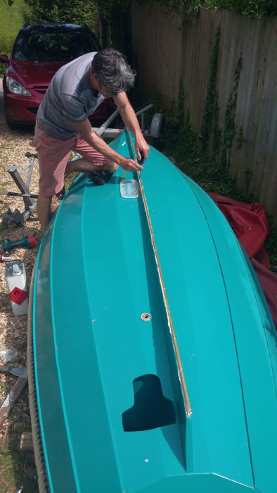 June, 2016. We were constantly dragged the boat up and down shingle beaches, so fitting a brass keel band during the recent restoration was an absolute necessity and one of the best things I've done for the boat's longevity. The outboard well's aperture is shaped for the motor's lower unit and propeller. I kept the cut-out to make a lid which fits into the hole from the inside; it reduces the drag and noise while I'm rowing.