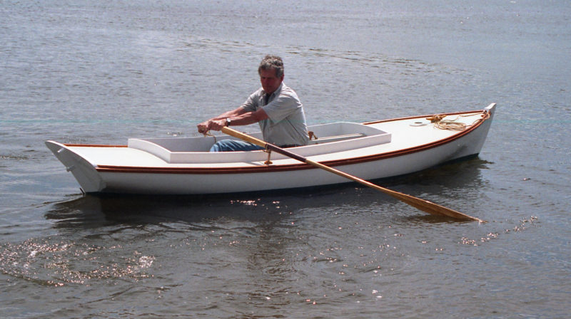 Barry Thomas, a Mystic Seaport boatbuilder who took part in building the Helen Packer, takes to the oars using a pair of tall oarlocks that keep the oars clear of the coaming. Boats similar to Seaford skiffs—sneakboxes and melonseed skiffs—were equipped with removable boxes that served as seats for rowing as well as for storage of small items. While none of the Seaford skiffs in the Mystic Seaport collection had such boxes present when the boats were acquired, the boxes were likely what were used for rowing.