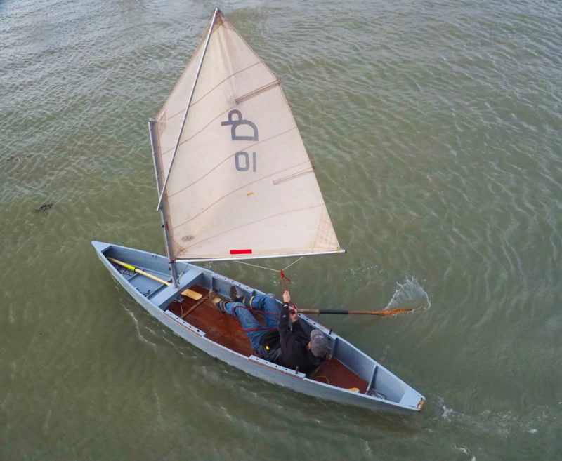Having just come about, the punt sailor has dropped his steering oar over the starboard rail. There is no accommodation for seating other than the cockpit sole.