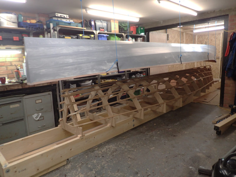 After the planking was completed, the hull was lifted and suspended by cords so the stringers and molds could be dismantled. The strongback remained to support and align the hull when it was set right-side up for the remainder of the construction.