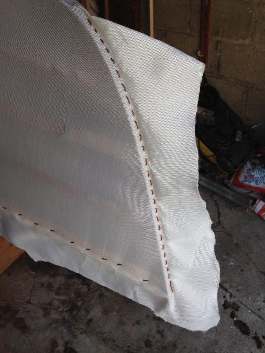 After the fabric has been tensioned along the stem and held by a row of stitching, the excess cloth is trimmed with a hot knife to keep it from unraveling.