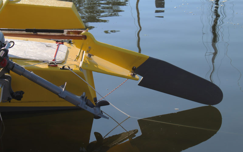 A hinged false transom allows the rudder to be kicked up. The tiller pulls the rudder up and holds it. The line at the bottom of the false transom holds the rudder down while the boat is underway.