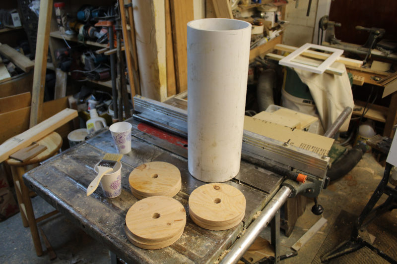 Ready for assembly: plywood disks, a cup of mixed epoxy, roller and black-pipe axle