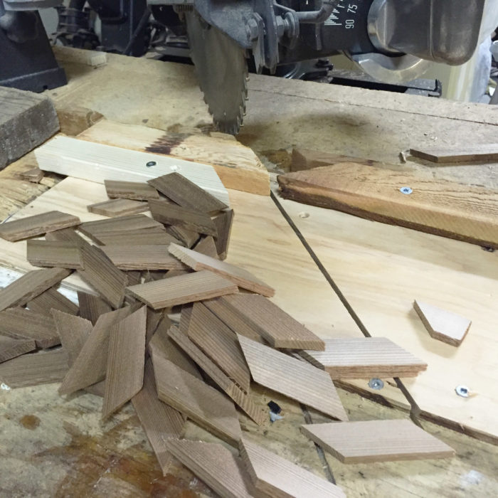 A radial arm saw was used to prepare the mountain of inlay pieces that would be needed for the build. Stops on the table made cutting the pieces quick work, but each had to be custom fit in its place on the curved surface of the hull.