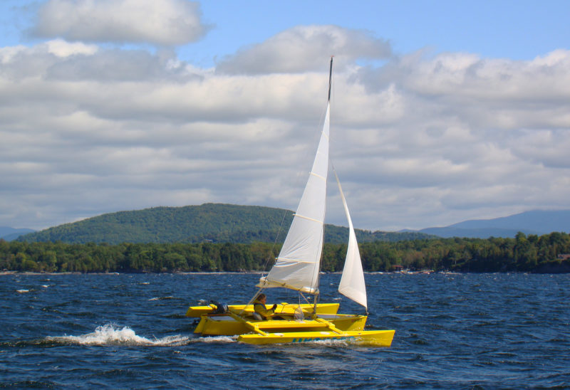 """LIMONADA owner Mac MacDevitt reports that his SeaClipper 16 is """"super fun in a stiff breeze."""" Here, sailing on Lake Champlain, just south of the Split Rock lighthouse he estimated his speed at about 13 knots. """"It was exciting, but I felt safe and secure."""""""
