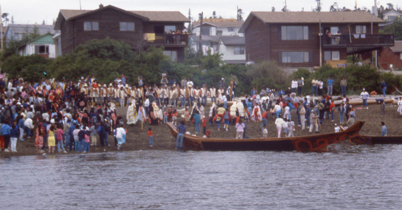 LOOTAAS came ashore to the enthusiastic welcome of the Bella Bella community. The paddlers are line up in their white vests at the top of the beach.