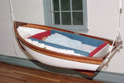 Thatcher, catching some shuteye here, was introduced to wooden boats at an early age, beginning with this cradle boat built by his father, Ken.