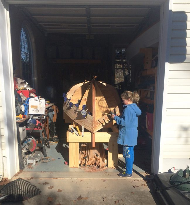 Younger sister Kyla was drafted into the effort to fill the screw holes left from attaching the Atlantic white cedar strips. She is now hooked and will start building her own boat this summer.