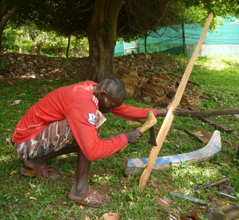 This is a very simple type of adze that I saw in many parts of Africa and used for countless purposes. Here the man is using his to trim down a board in order to make a tight fit in the boat.